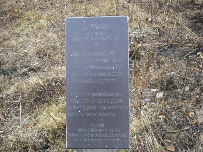"The art project is called ""On Prairie."" The caption on this plaque reads: "" In 1999 a White House Council recognized the Paint Creek Trail as Michigan's Millennium Legacy Trail. This sculpture installation celebrates prairie restoration along the trail. The form of the central copper piece is derived from bur oak and grasses, representing plants in prairie remnants, and fire, for restorative burning."""